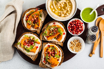 snack breads with hummus and baked pumpkin on a serving board with arugula pesto. seeds of pomegranate and pine nuts. healthy food