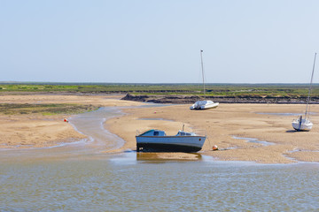Motor boat beached at low tide