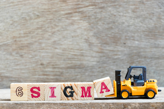 Toy forklift hold letter block A to complete word 6 sigma on wood background
