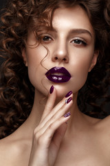Beautiful girl with evening make-up, purple lips, curls and design manicure nails. beauty face. Photos shot in studio.