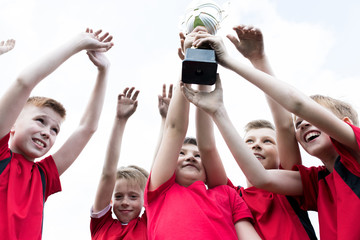 Low angle portrait of junior football team holding trophy together and cheering happily after winning match