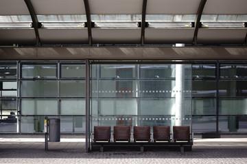 Glasunterstand Bushaltestelle / Der neue gebaute Glasunterstand einer modernen Bushaltestelle an einer Straße.
