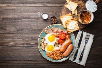 Full English breakfast with fried eggs, sausages, bacon, beans, mushrooms, tomatoes on a plate, bread toasts with butter. Traditional British meal, top view, rustic wooden background, space for text.