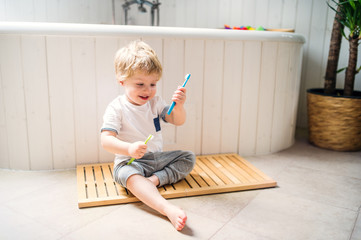 A toddler boy with a toothbrush sitting on the floor in the bathroom at home.