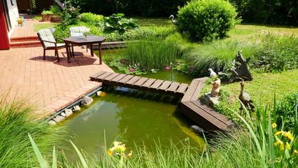 attraktiver naturbelassener Teich an rote Terrasse angrenzend mit Brücke und Tisch und Stühlen