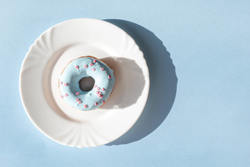 Donut covered with blue glaze and sprinkled with small pink hearts on a white plate on blue background under natural light with shadows
