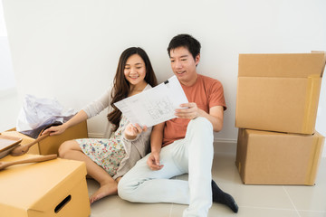 Couple read blueprint at new house