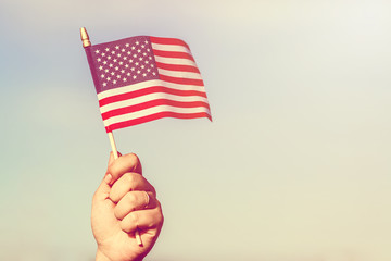 Woman hand holding american flag of the USA with stars and stripes against blue sky. Vintage toned effect.