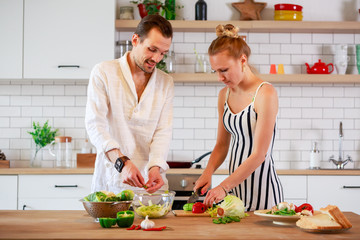 Picture of young couple in love preparing breakfast in kitchen