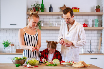 Image of parents with daughter cooking food in kitchen
