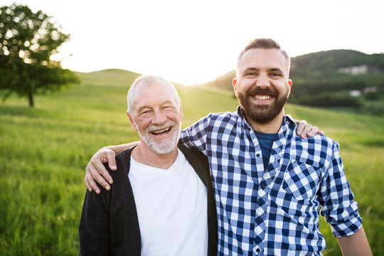 A portrait of an adult hipster son with senior father in nature at sunset, arms around each other.
