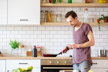 Photo of man with frying pan and phone in hands in kitchen