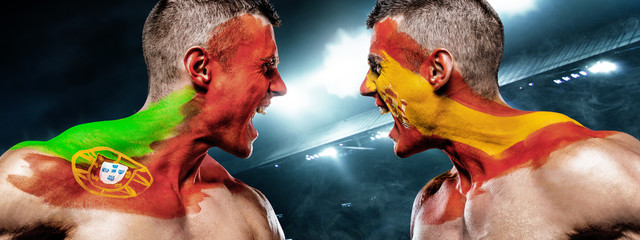 Portugal vs Spain. Two soccer or football fans with flags face to face on stadium.