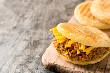 Arepa with shredded beef and cheese on wooden background. Venezuelan typical food. Copyspace