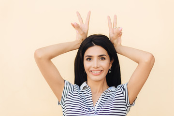 Portrait of happy brunette female makes horn gesture, has fun and foolishes with friends, being in good mood, wears casual outfit, smiles broadly at camera, shows braces on teeth. Funny woman indoor