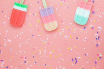Table top view aerial image of food for summer holiday background concept.Flat lay arrangement variety ice cream pop stick on modern rustic pink paper wallpaper at office desk.Pastel tone design.