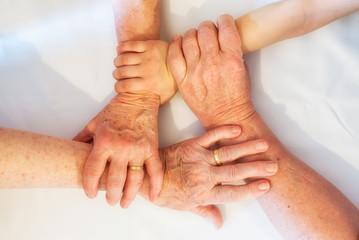 Hände mehrerer Generationen greifen ineinander.