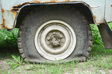 Flat tire on an old rusty SUV close-up.