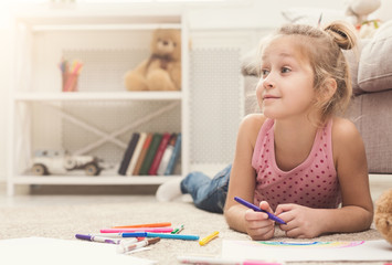 Smiling little girl drawing with colored pencils