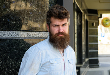 Man with beard and mustache on strict, serious or disgusting face, black marble background. Masculinity concept. Hipster with tousled hair and long beard looking at camera.