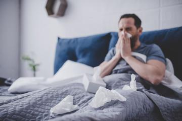 Man sneezing in napkin