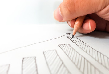 drawing a growing graph for Concept of Business success foundation, on white paper background.