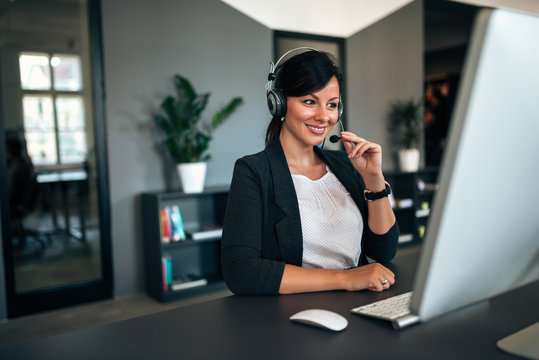 Beautiful woman with headset sitting in front of computer.