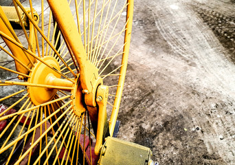 Parked back wheels of old style Yellow bicycle on the road background design for advertising.