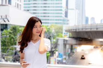 Portrait charming beautiful young asian woman. Attractive woman is talking or chatting with her boyfriend by using smartphone and hand free for small talk with him. city background, copy space