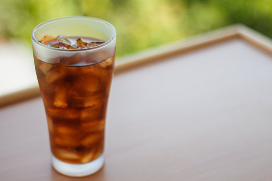 Cola in glass with ice cubes and blur background. Sparkling water soft drinks.