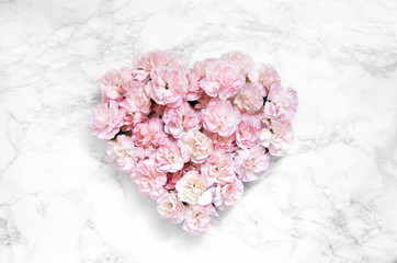 Heart made of pink carnations on marble background. Flat lay, top view