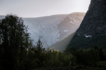 Sunrise in a mountain valley with forest in Norway
