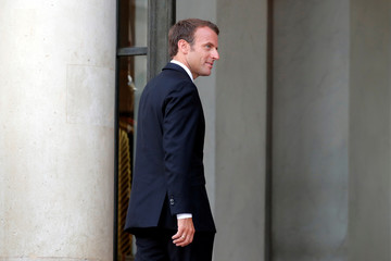 French President Emmanuel Macron walks back inside the Elysee Palace in Paris