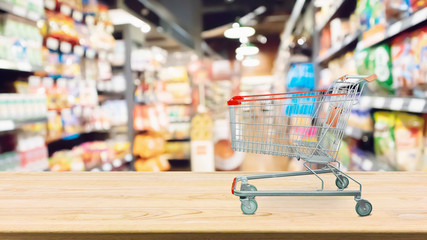 Abstract blur supermarket shelves defocused background with shopping cart on wood table