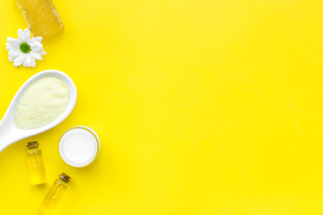 Natural organic spa cosmetics for skin care with chamomile. Spa salt, cream, soap, oil on yellow background top view copy space