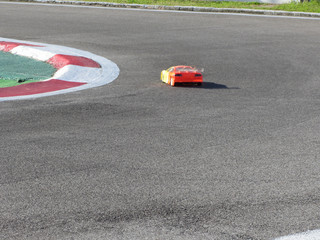 Small radio controlled model car on the track . Miniature remote controlled sport racing cars hobby