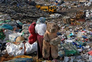 Woman carries stuffed toys through a dump site in Mumbai