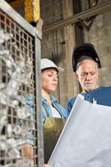 Zwei Metallarbeiter schauen auf Bauplan