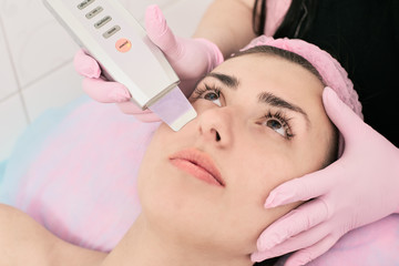 Young woman getting ultrasound therapy of face in beauty salon