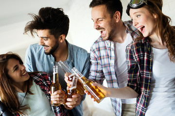 Group of happy young friends having fun and drinking beer