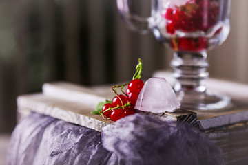 Red currant and ice cubes in a transparent glass on the table
