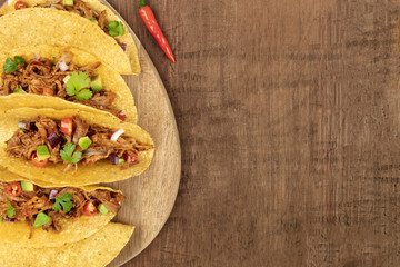Overhead closeup photo of Mexican tacos with pulled meat, avocado, chili peppers, cilantro, with copy space