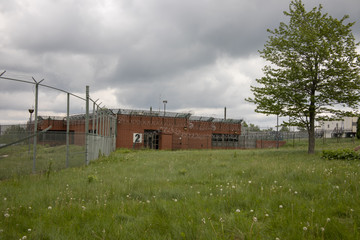 Priso with razor wire on fence with overgrown yard
