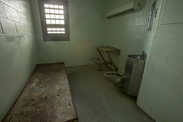 Metal bed inside solitary confinement cell