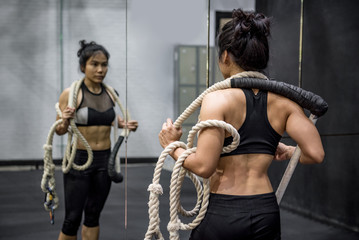 Young Asian gymnast woman carrying ropes on shoulders for gymnastic exercise in fitness gym