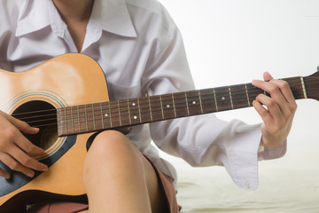 young Asian woman hands touching guitar chords