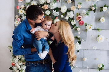 A one-year-old child is embarrassed and laughs at the kisses of her parents. Dad keeps the girl in her arms, and Mom hugs them.