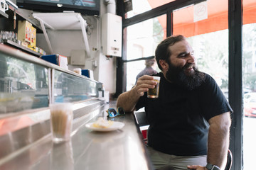 Bearded man who drinks beer in a bar in Madrid city
