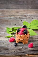 Ripe raspberries with blackberry in a basket.