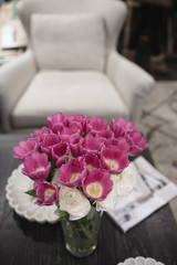 Pink flowers stand on a wooden table
